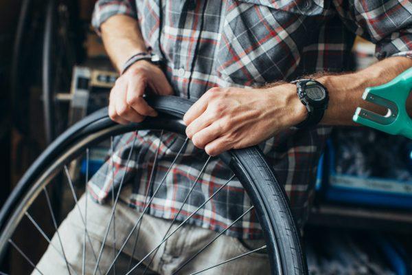 man adjusting a bike tire